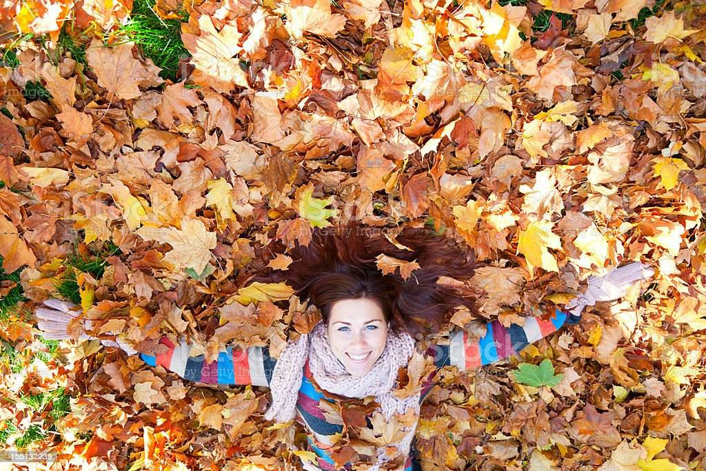 Woman with red hair laying on autumn leaves. royalty-free stock photo