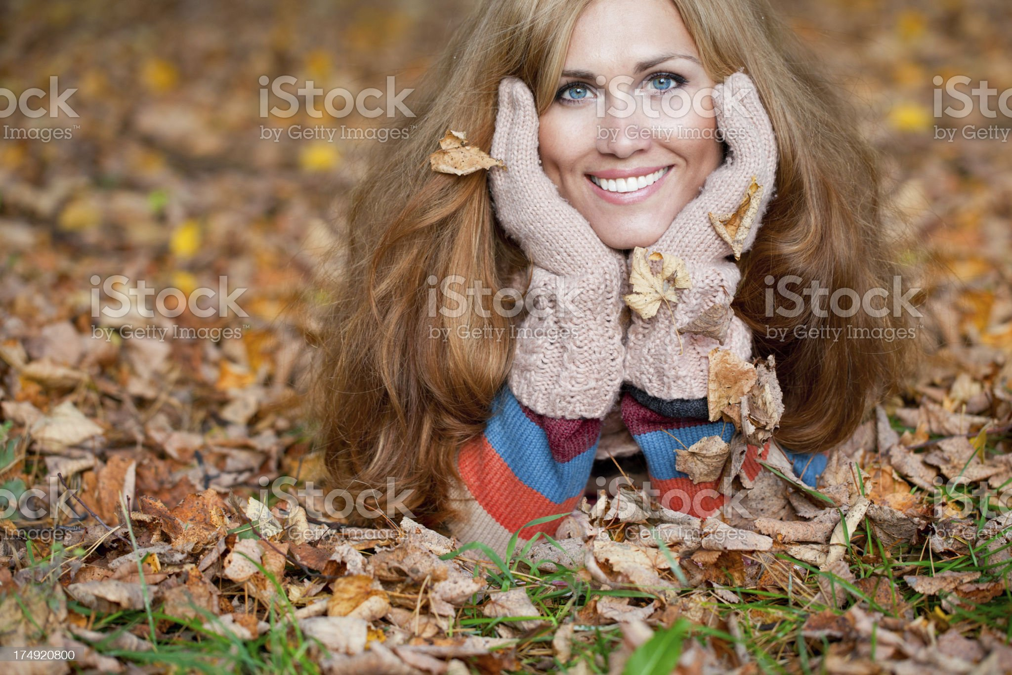 Woman with red hair laying on autumn leaves royalty-free stock photo