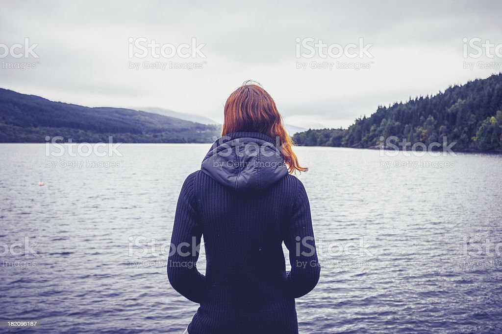 Woman with red hair standing in front of lake watching hills stock photo