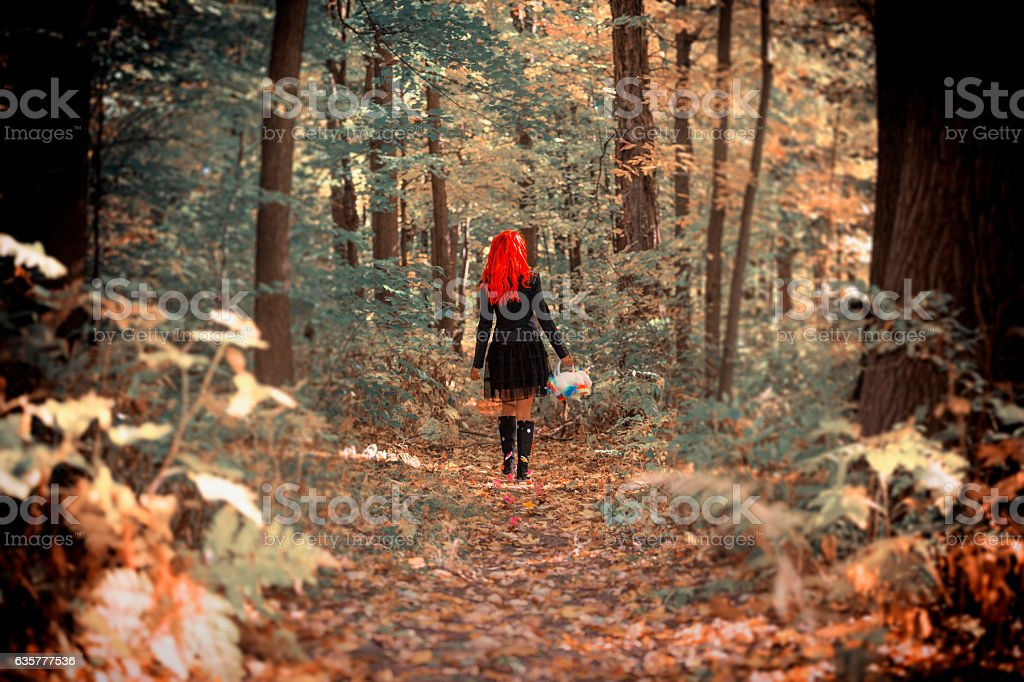 Woman with red hair walking in the forest stock photo
