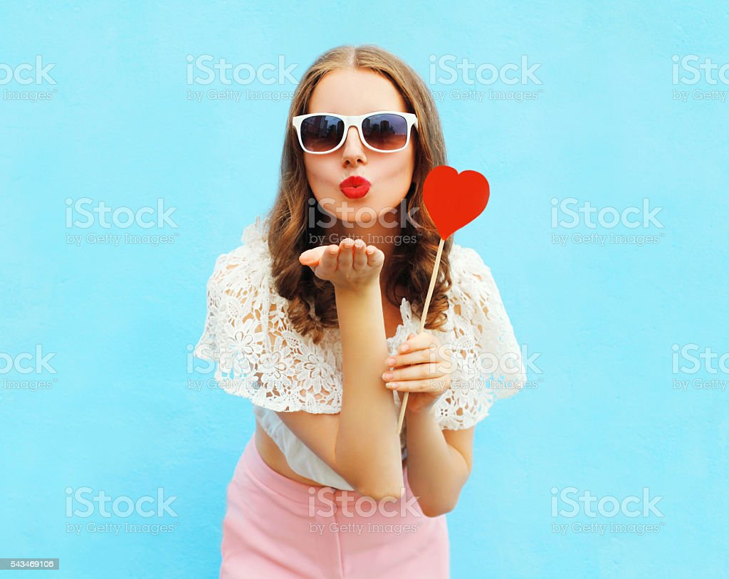 woman with red heart lollipop sends air kiss over stock photo