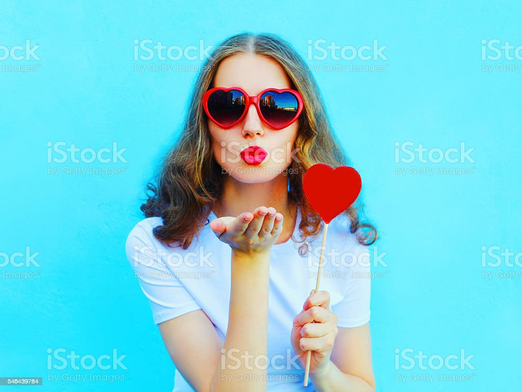 woman with red heart lollipop sends an air kiss stock photo