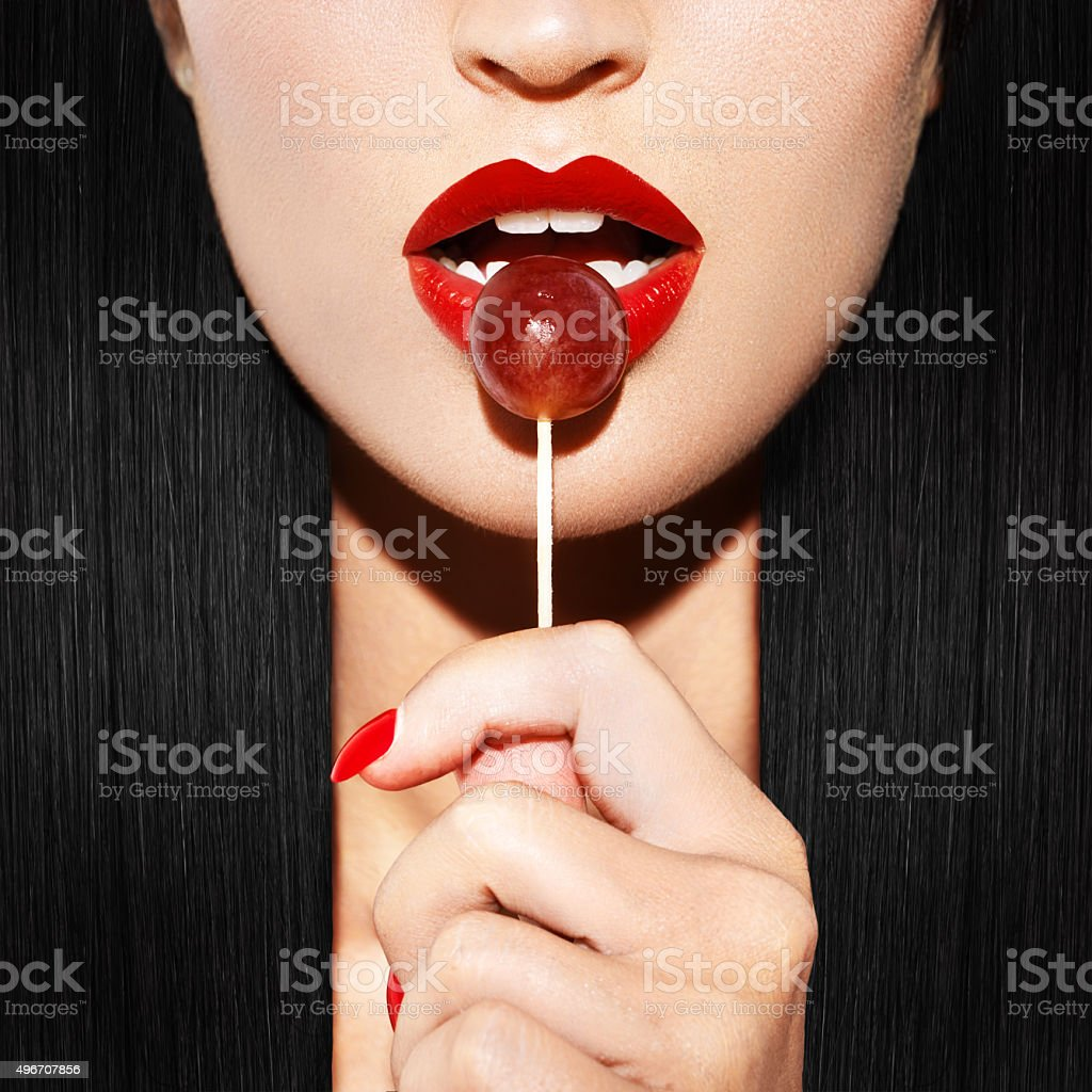 Woman with red lips holding lollipop stock photo
