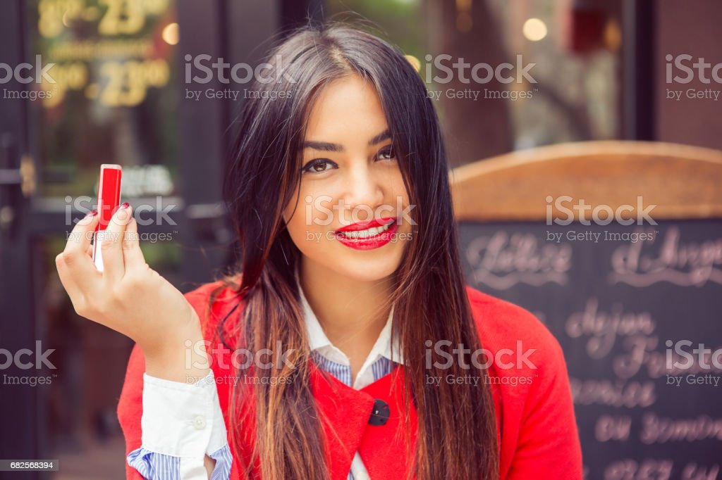 Woman with red lips showing lipstick, outdoors coffee shop background. closeup portrait positive female, facial expression stock photo
