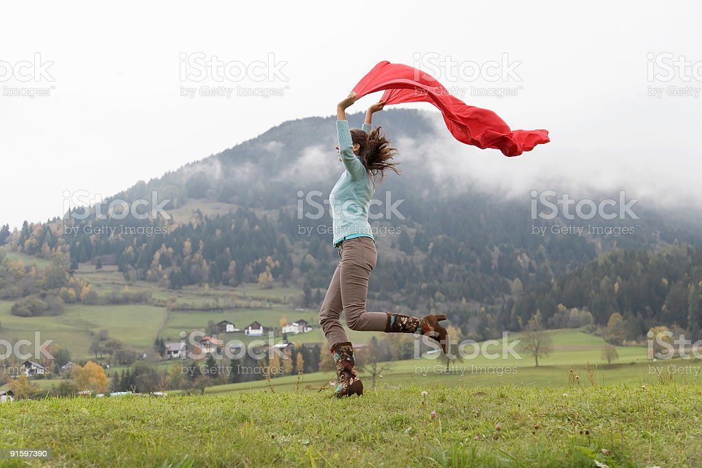 Woman with red scarf jumping for joy in mountain area royalty-free stock photo
