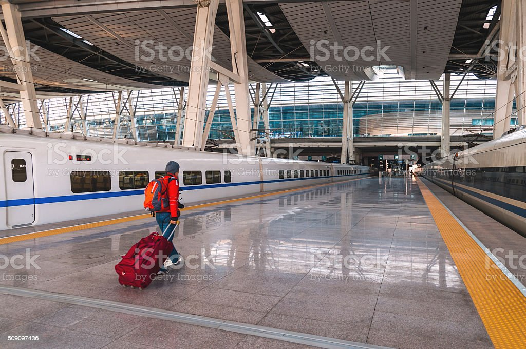 Woman with Red Suitcase in  Beijing Railway Station, Beijing, China stock photo