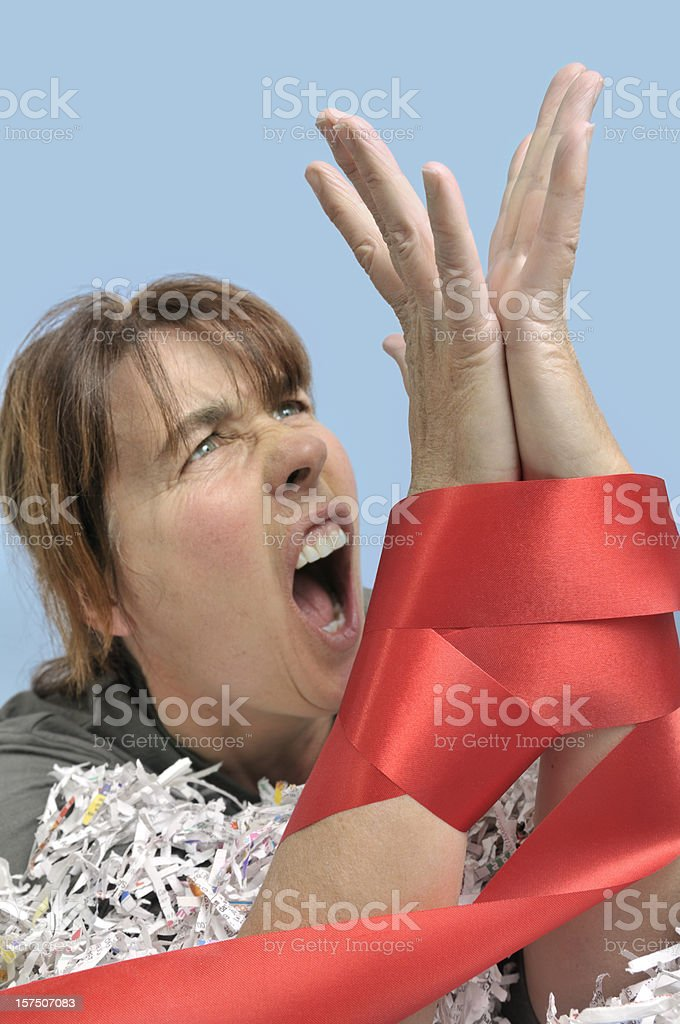 Woman with red tape and shredded paper stock photo