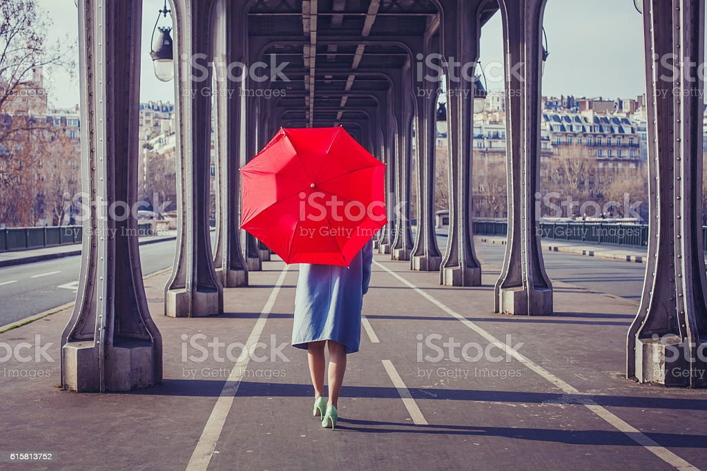 woman with red umbrella walking on the street of Paris stock photo