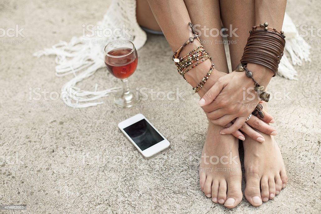 Woman with red wine and cell phone outdoors stock photo