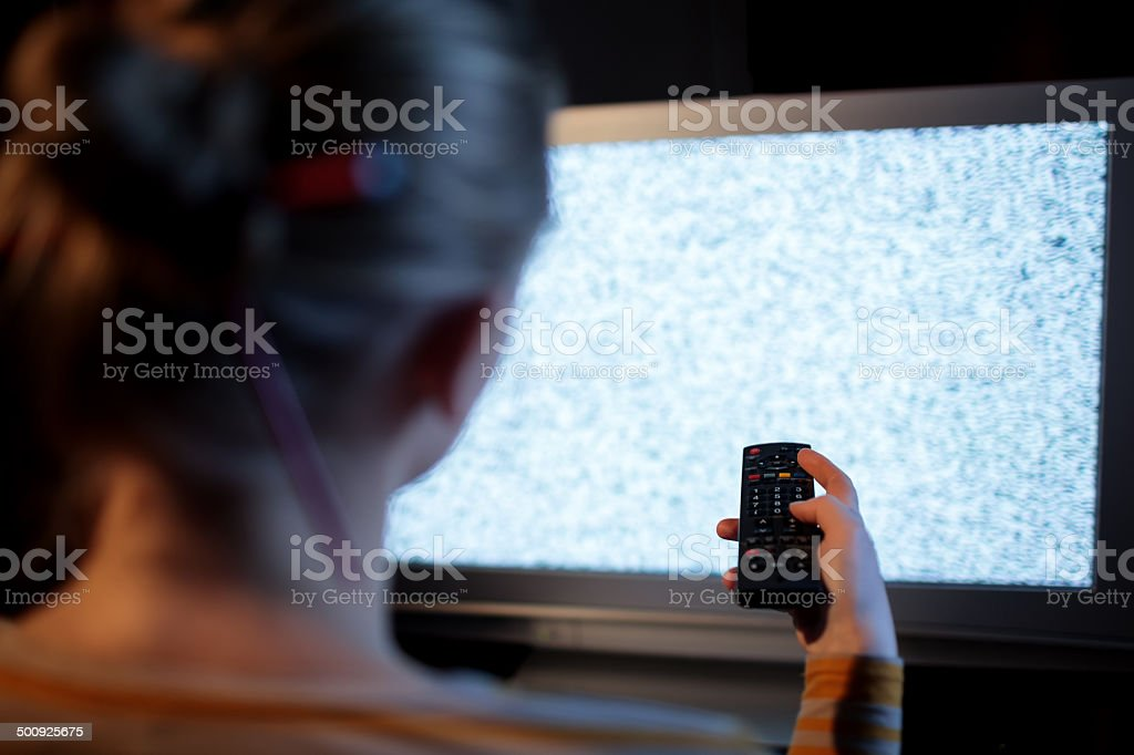 Woman with remote control in front of TV set stock photo