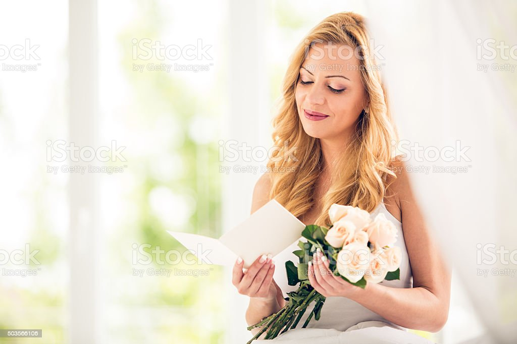 Woman with roses reading greeting card stock photo