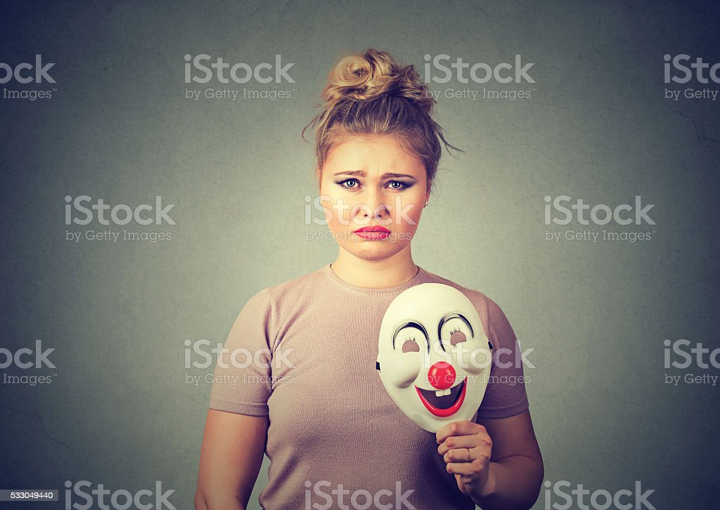 woman with sad expression holding clown mask stock photo