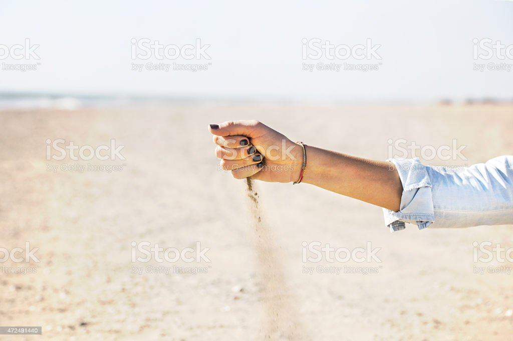Woman with sand falling through her hands on the beach stock photo
