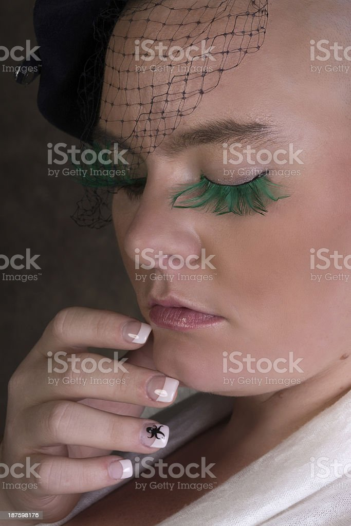 Woman with shaved head and green eyelashes, closeup. royalty-free stock photo