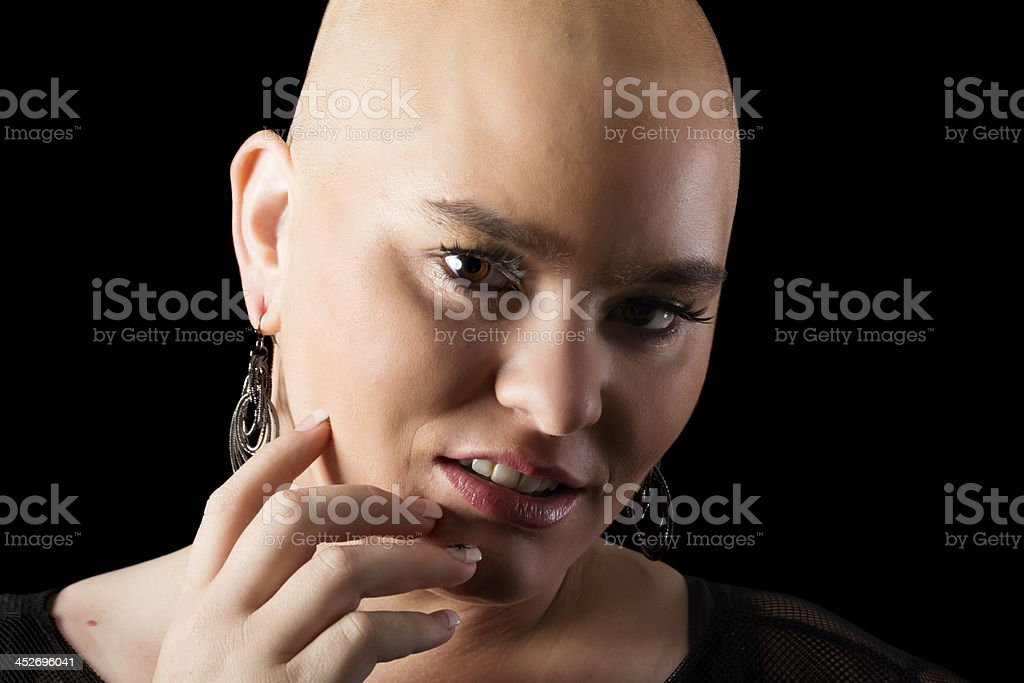 Woman with shaved head regarding camera. royalty-free stock photo