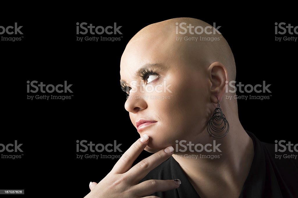 Woman with shaved head smiling, touching chin. royalty-free stock photo