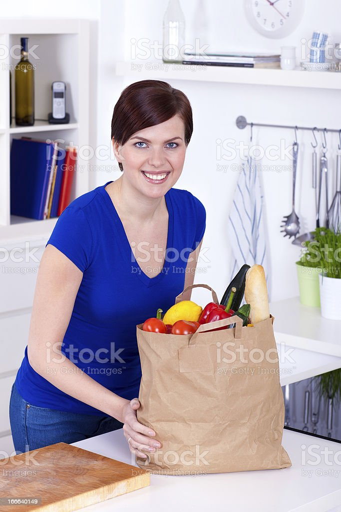 Woman with shopping bag in the kitchen royalty-free stock photo
