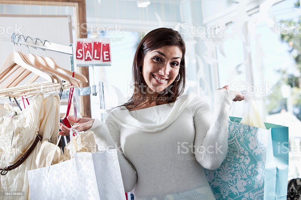 Woman with shopping bags by sale rack stock photo