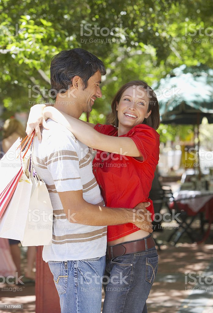 Woman with shopping bags embracing man stock photo