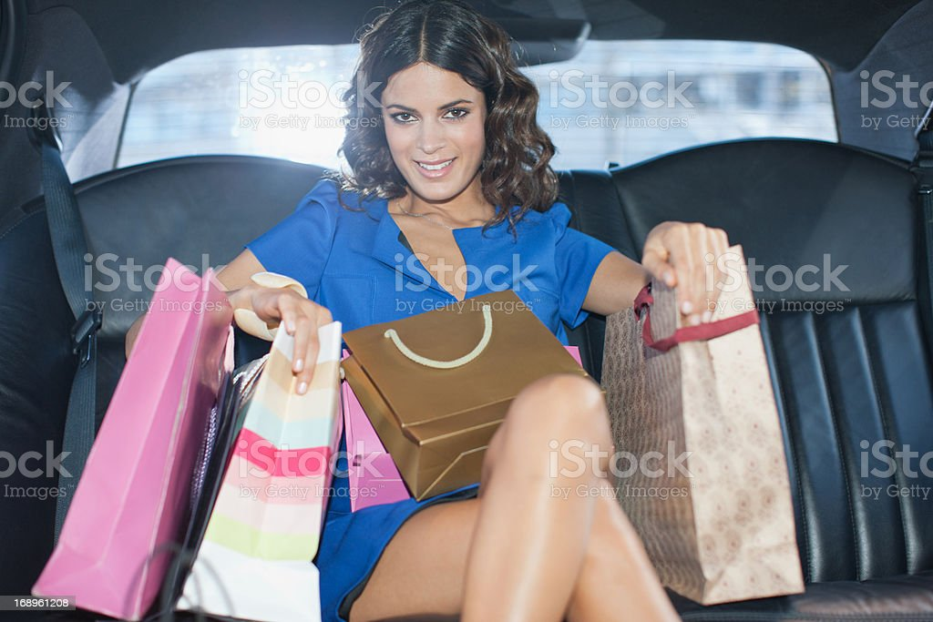 Woman with shopping bags in backseat of limo royalty-free stock photo