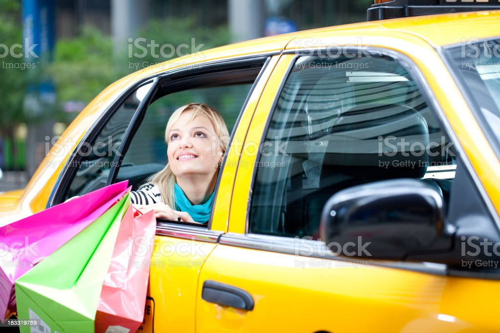 Woman with shopping bags in New York City yellow cab stock photo