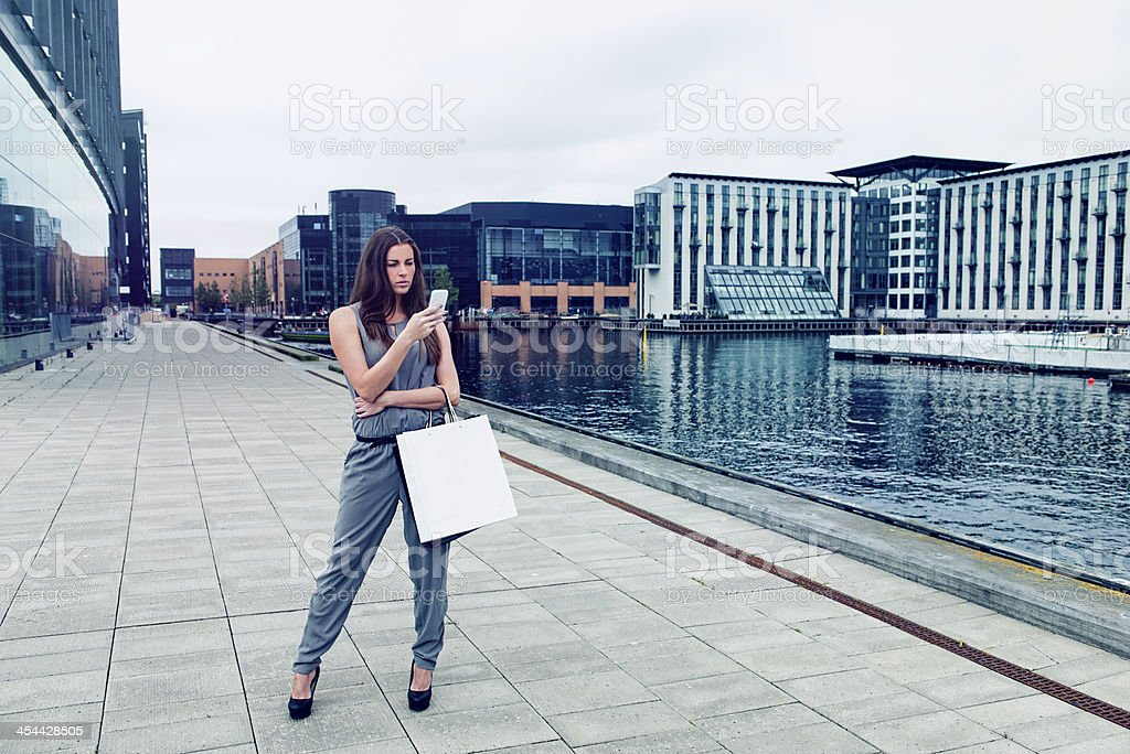 Woman with shopping bags looks at her phone royalty-free stock photo