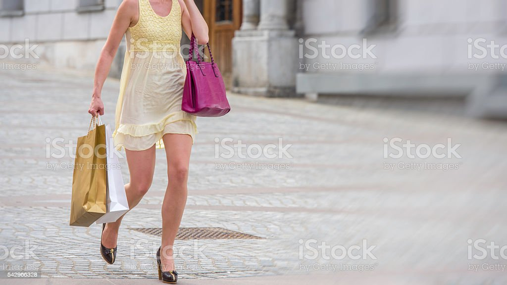 Woman with shopping bags running down the street stock photo