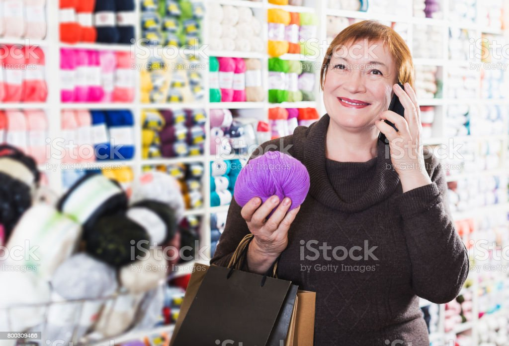 Woman with shopping bags using phone stock photo