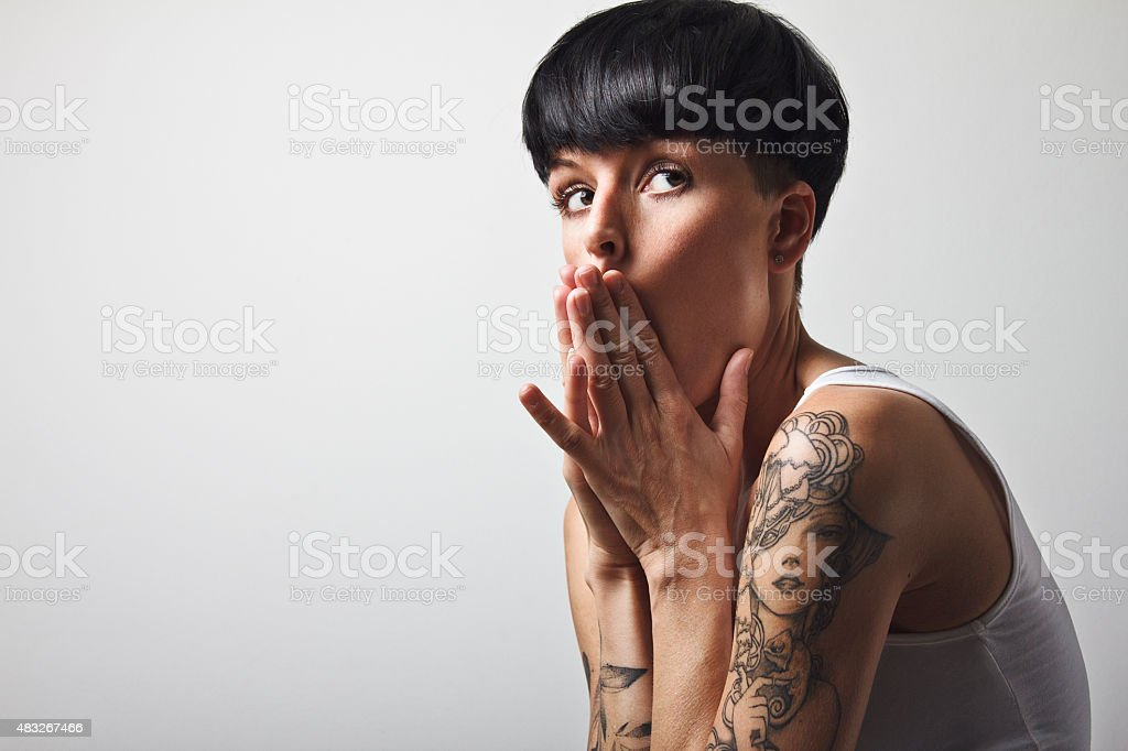 Woman with short black hair and tattoos stock photo