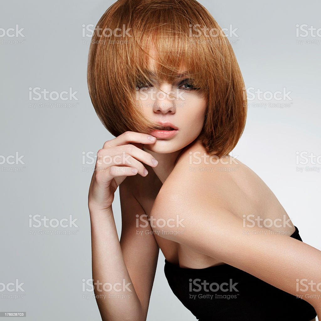 A woman with short red hair posing for the camera stock photo