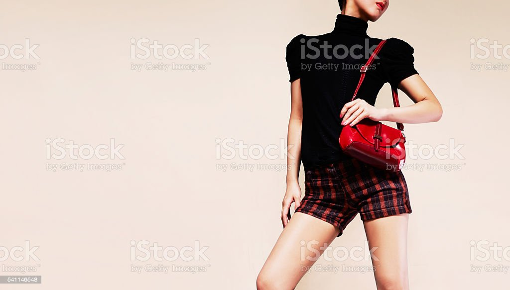 Woman with shorts holding red handbag purse. Fashion image. stock photo
