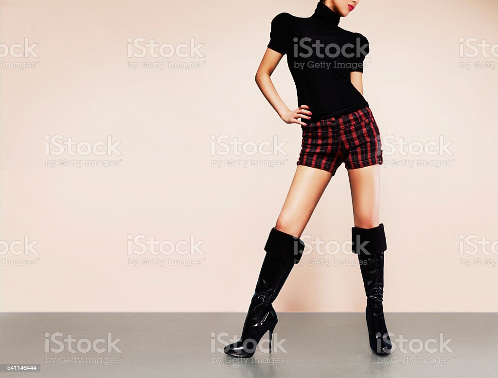 Woman with shorts with black heels boots. Fashion image. stock photo