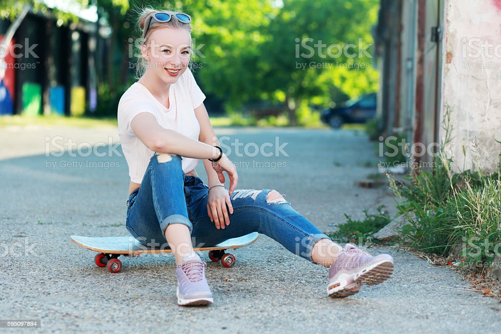 Beautiful young woman with skateboard Fashion style Urban background
