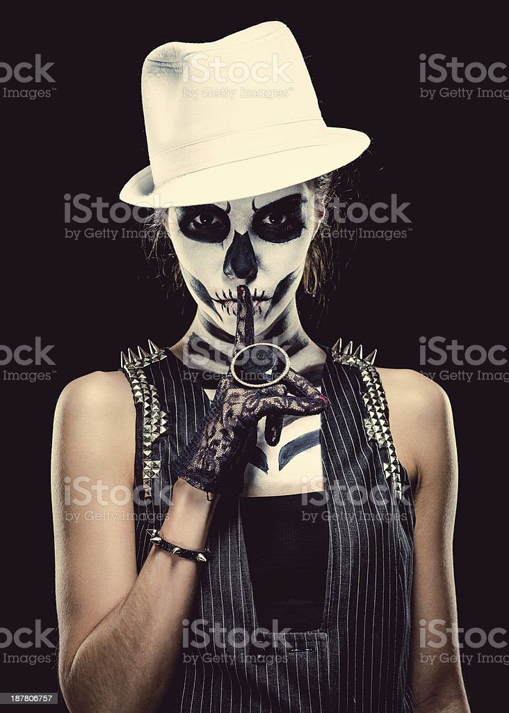 Woman with skeleton face art making a hush gesture stock photo