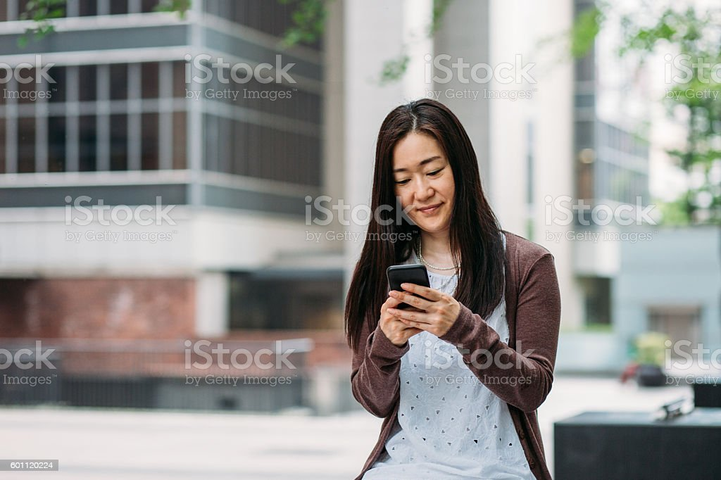 Woman with smart phone outdoors stock photo
