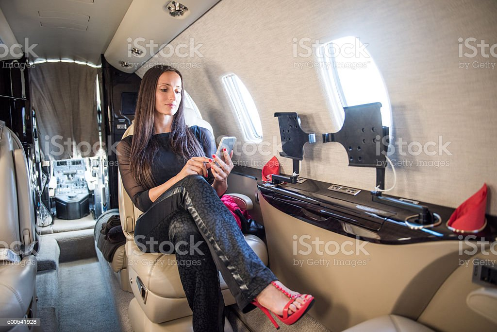 Woman with smart phone sitting in private jet airplane stock photo