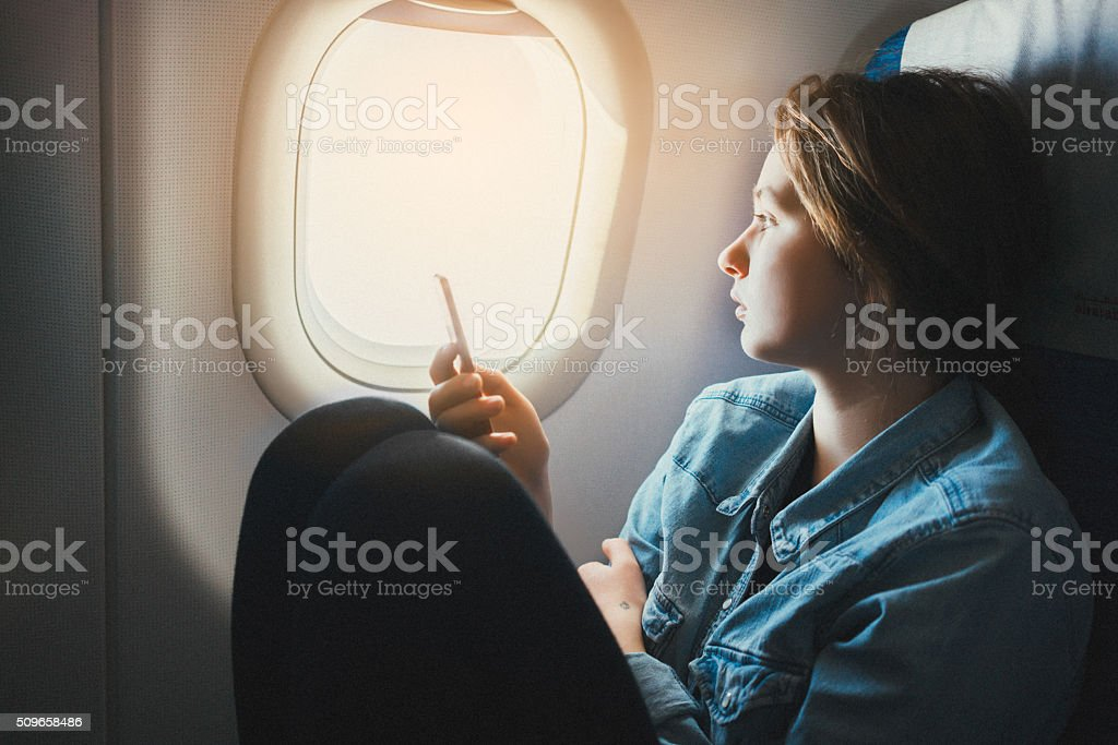 Woman with smartphone in airplane stock photo