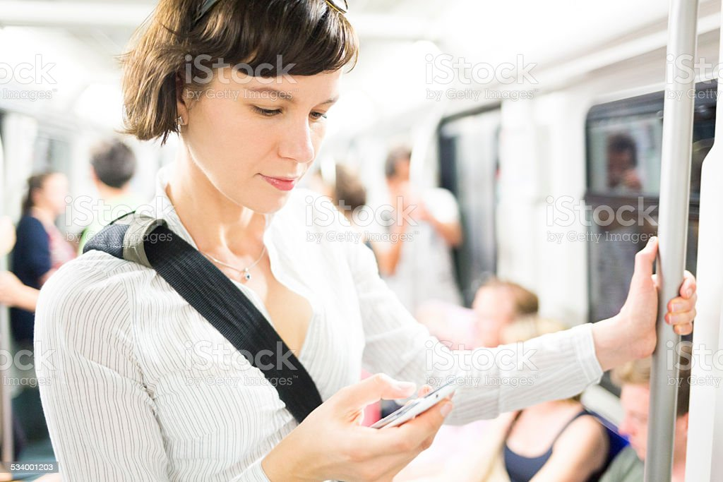 Woman with smartphone in subway stock photo