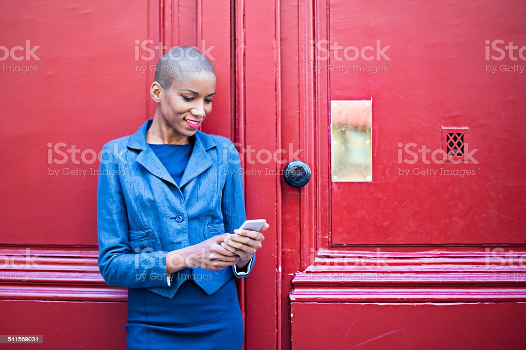 Woman with smartphone standing in front of wooden red door stock photo