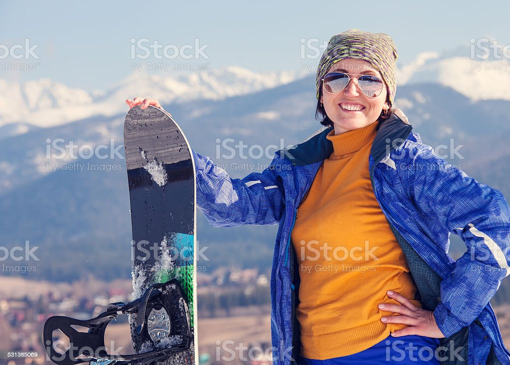 Woman with snowboard on the snow hill stock photo