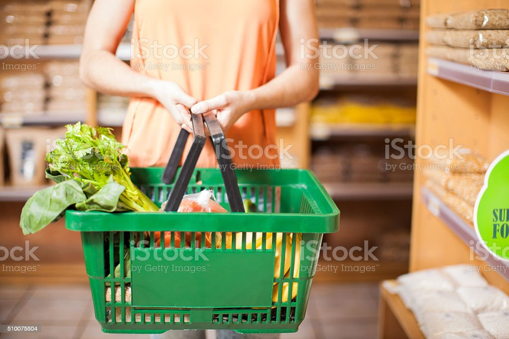 Woman with some groceries in a basket stock photo