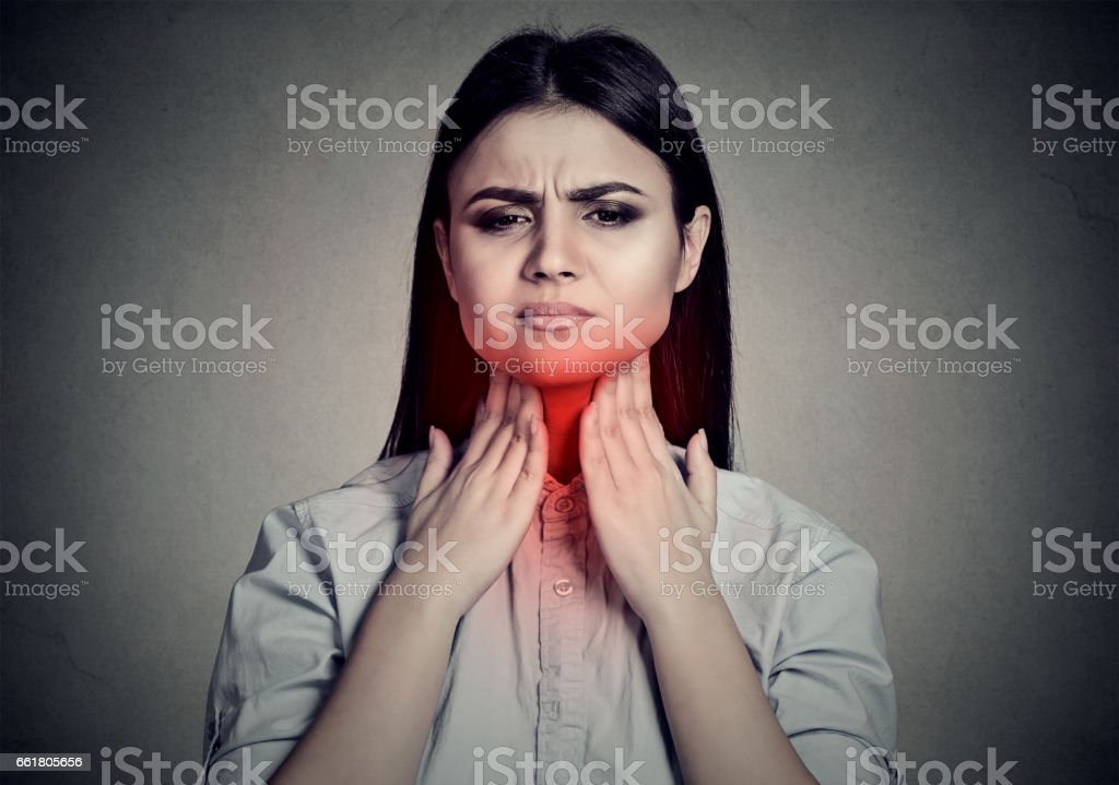 Woman with sore throat touching her neck stock photo