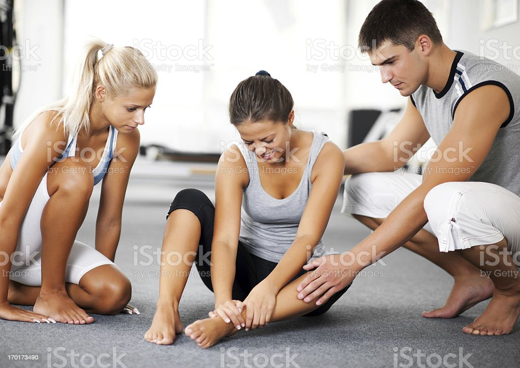 Woman with sprained ankle and her two friends stock photo