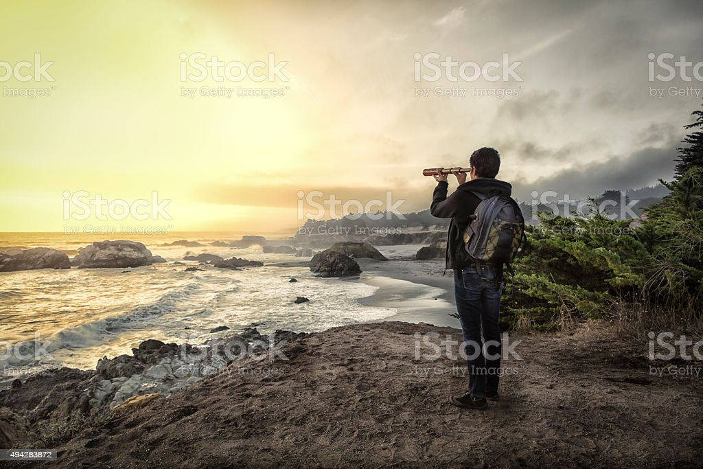 Woman with spyglass looking toward ocean stock photo