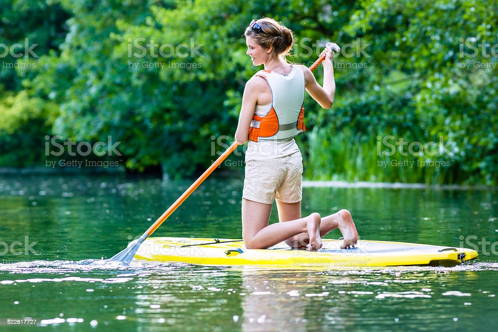 Woman with stand up paddle board sup on river stock photo