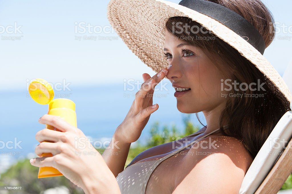 Woman with straw hat applying sunblock to face outdoors stock photo