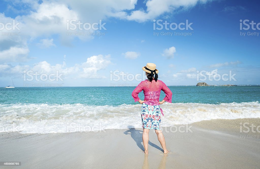 Woman with Straw Hat Looking Out into the Caribbean Sea stock photo