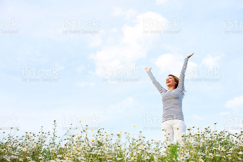 Woman with stretched arms in flower field stock photo