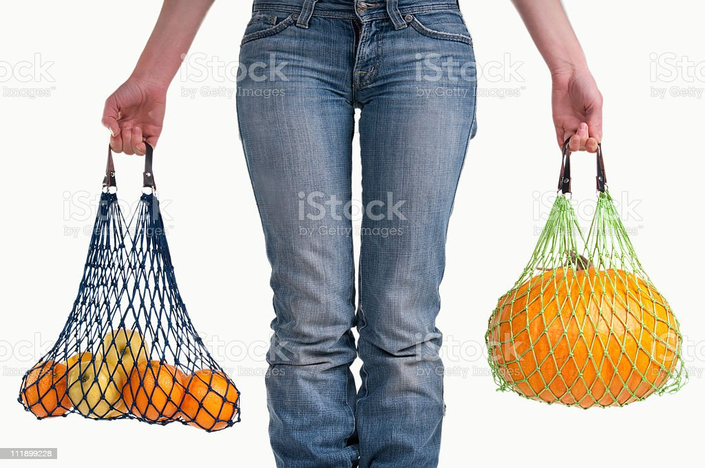 Woman with string shopping bags (Einkaufsnetz) carrying different yellow fruits royalty-free stock photo