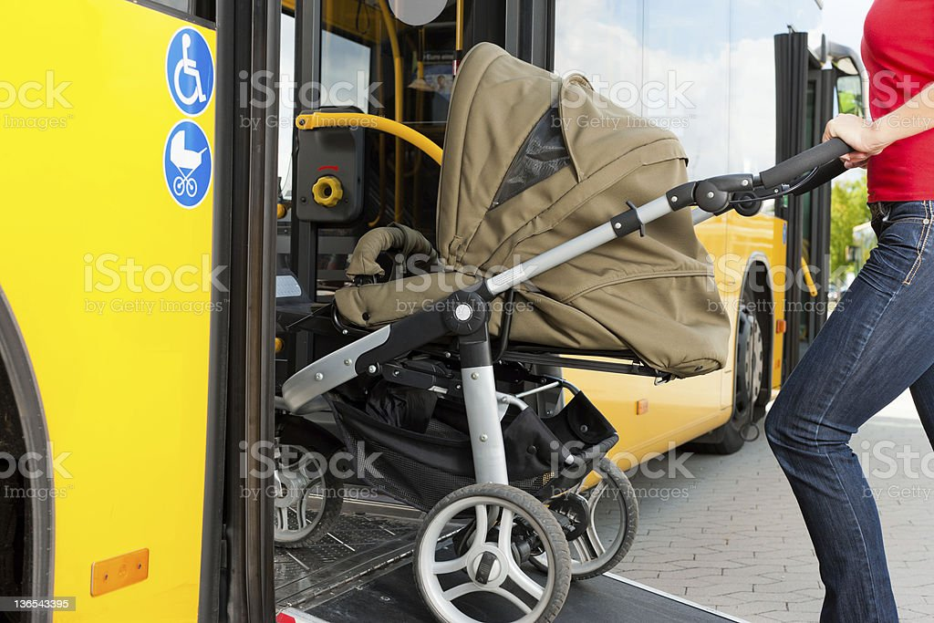 Woman with stroller getting into a bus stock photo